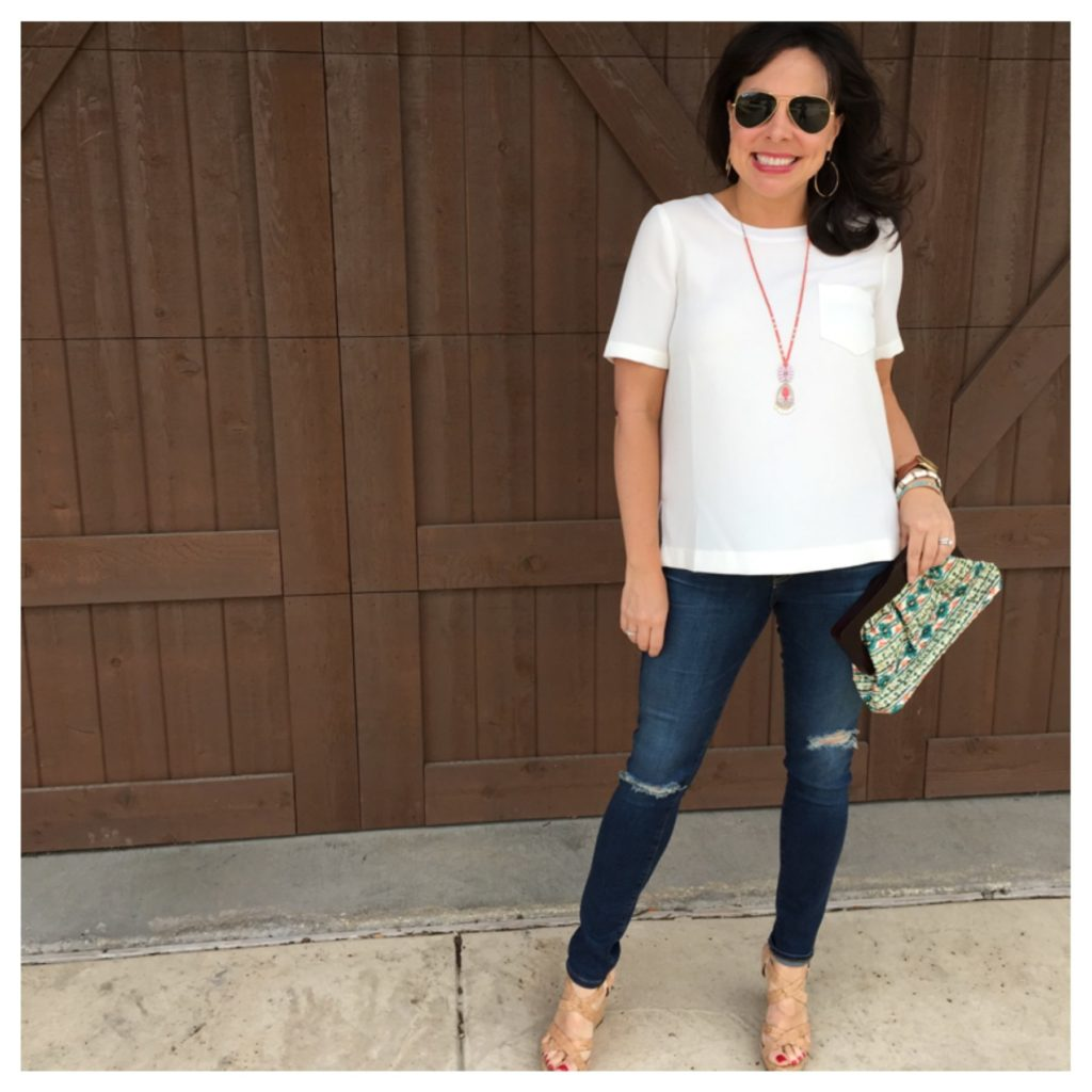 white blouse, jeans, and cork clutch